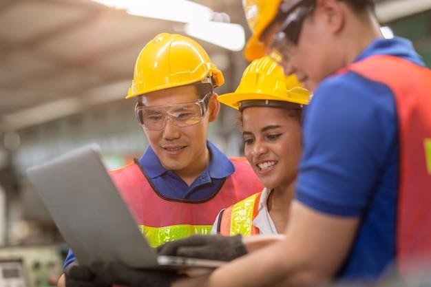Le donne ingegneri che lavorano con la squadra maschile mescolano il lavoro di gara aiutano insieme nell'industria pesante con la discussione del computer portatile, si uniscono al buon lavoro di squadra del partner.