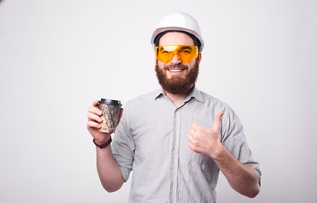 Uomo dell'operaio dell'ingegnere che indossa il casco bianco bere un caffè da asporto e mostrare il pollice in su