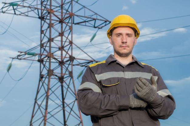 Ingegnere: un operaio in indumenti protettivi e un casco, con guanti da lavoro in mano.