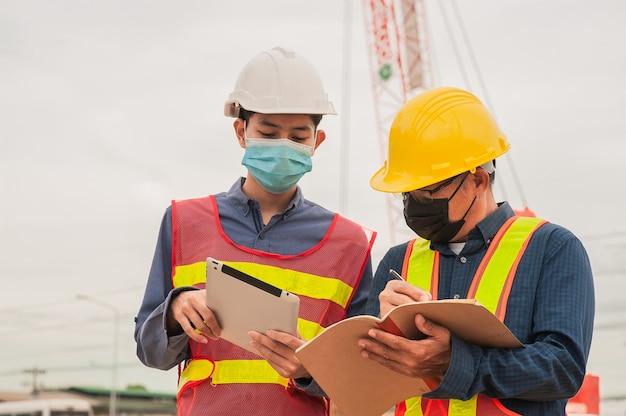 Ingegnere lavoratore che lavora lavoro di squadra sulla costruzione del sito, l'uomo indossa la maschera covid19