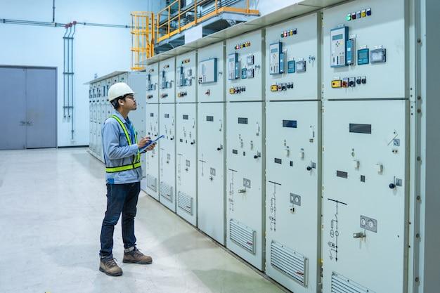 Ingegnere che lavora e controlla la distribuzione di energia elettrica del quadro di stato nella sala sottostazione, i tecnici della manutenzione controllano il concetto elettrico del sistema di protezione del relè, quadro di media tensione