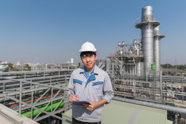 Ingegnere che lavora e valvola di ritegno nella fabbrica della centrale termoelettrica