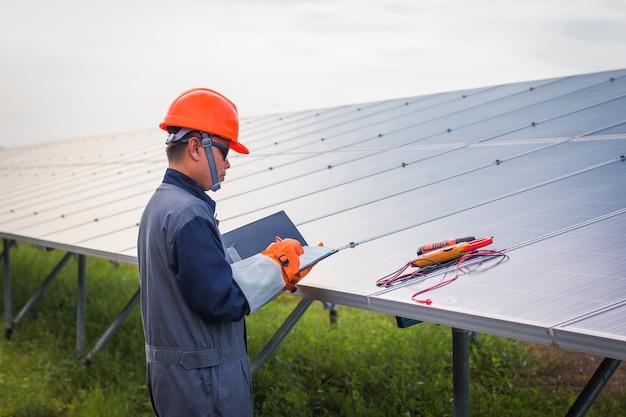 Ingegnere che lavora sul controllo delle attrezzature nella centrale elettrica solare