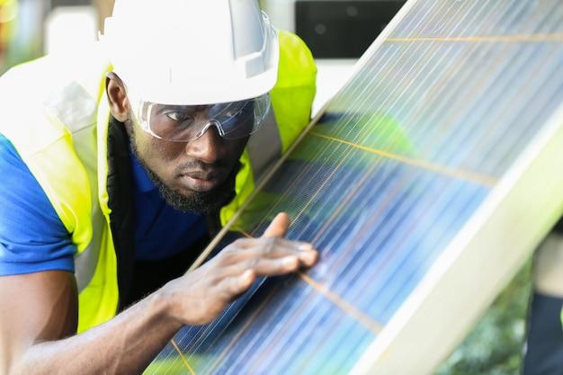 Ingegnere che lavora su apparecchiature di controllo e manutenzione presso centrale elettrica di pannelli solari, parco di celle fotovoltaiche, concetto di energia verde.