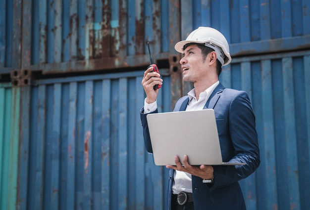 Ingegnere che lavora nel cantiere per la costruzione di container, cantiere industriale per container per l'importazione e l'esportazione per affari, controllo caposquadra container industriale nave da carico merci nella zona industriale