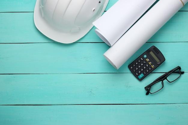 Area di lavoro dell'ingegnere. casco da costruzione, rotoli di disegni, calcolatrice e bicchieri su uno sfondo di legno blu. vista dall'alto. copia spazio