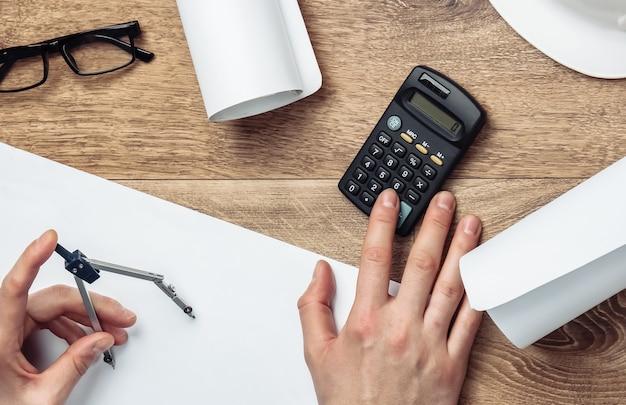 Area di lavoro dell'ingegnere. le mani degli uomini contano sulla calcolatrice il costo di costruire una casa su un tavolo di legno.