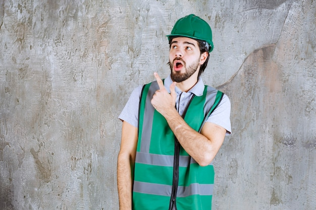 Ingegnere in marcia gialla e casco in piedi sul muro di cemento e mostrando qualcosa.