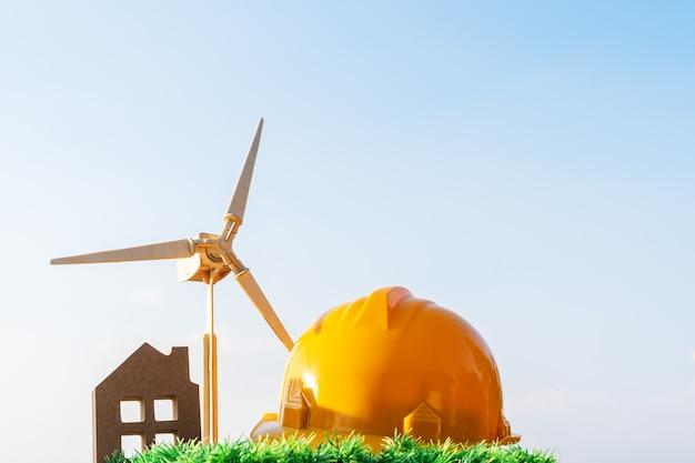 Ingegnere giallo cappello casa turbina eolica su sfondo di erba ambiente eco idee energia rinnovabile