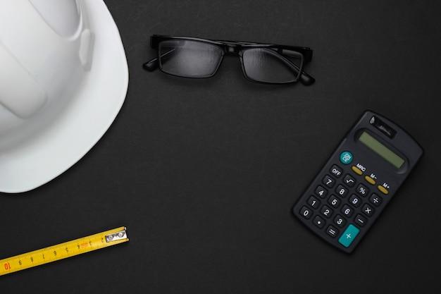 Ingegneria e attrezzature per l'edilizia su sfondo nero. casco da costruzione, calcolatrice, occhiali, righello. vista dall'alto