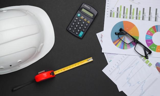 Ingegneria e attrezzature per l'edilizia su sfondo nero. casco da costruzione, calcolatrice, righello, occhiali, grafici e grafici. analisi economica. vista dall'alto