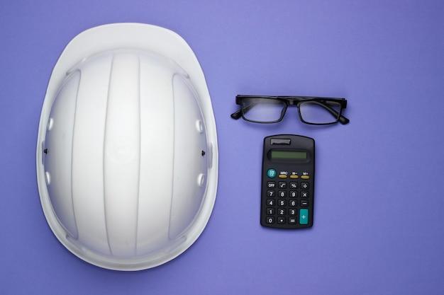 Ingegneria e attrezzature per l'edilizia su sfondo viola. casco da costruzione, calcolatrice, occhiali. vista dall'alto