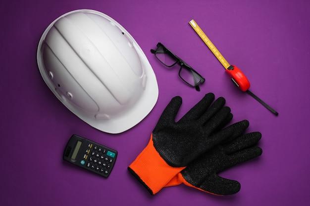 Ingegneria e attrezzature per l'edilizia su sfondo viola. composizione lat piatta. vista dall'alto