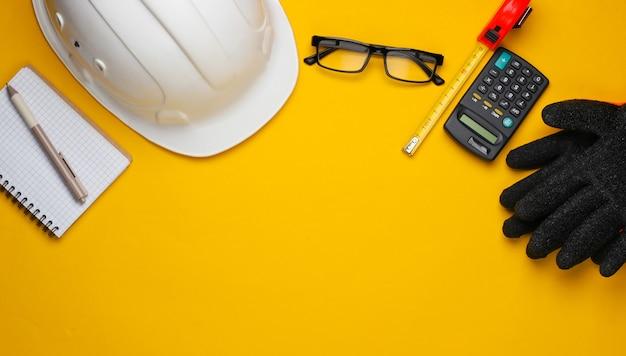 Ingegneria e attrezzature per l'edilizia su sfondo giallo. composizione lat piatta. vista dall'alto. copia spazio