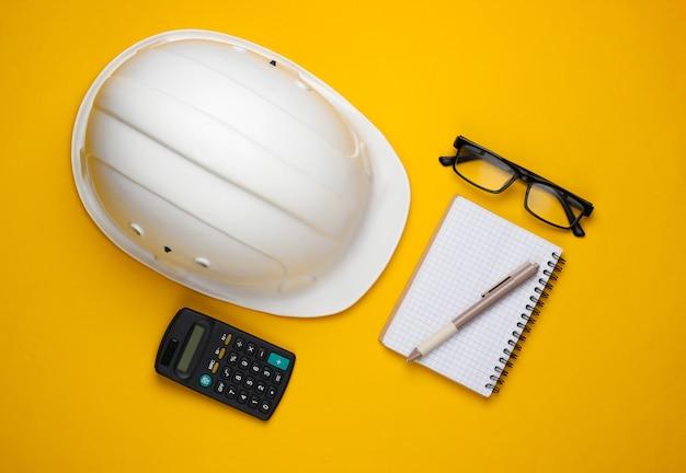 Ingegneria e attrezzature per l'edilizia su sfondo giallo. composizione lat piatta. vista dall'alto