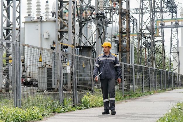 Un impiegato di ingegneria fa un giro e un'ispezione di una moderna sottostazione elettrica. energia. industria.