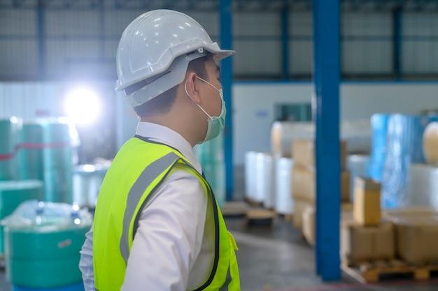 Un ingegnere che indossa una maschera medica, un casco protettivo che lavora nella fabbrica del magazzino warehouse