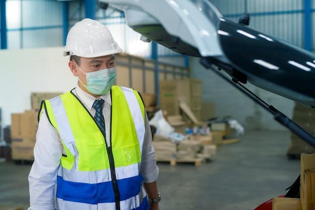 Un ingegnere che indossa una maschera medica, un casco protettivo che lavora nella fabbrica del magazzino