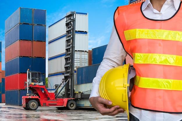 Uomo di ingegneria con il casco di sicurezza giallo che sta davanti al carrello elevatore che tratta il contenitore di contenitore nella zona logistica