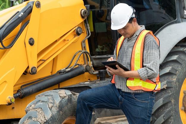 Ingegneria che indossa un casco di sicurezza bianco in piedi davanti all'escavatore a cucchiaia rovescia guardando a casa i lavori di costruzione