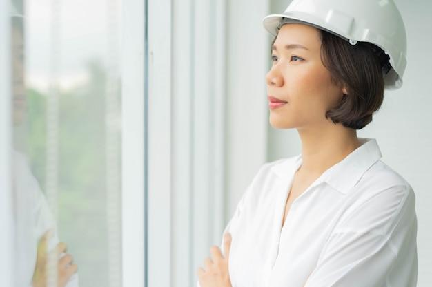 Braccio donna ingegneria croce e guardando fuori ufficio con visione per uno stile di vita di successo