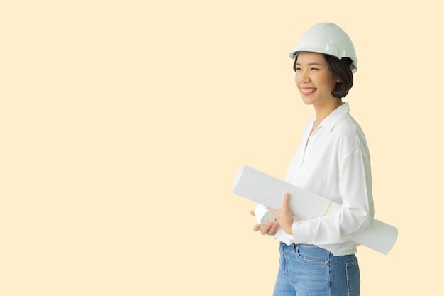 Donna di ingegneria isolata su sfondo color crema per il concetto di progetto di edifici