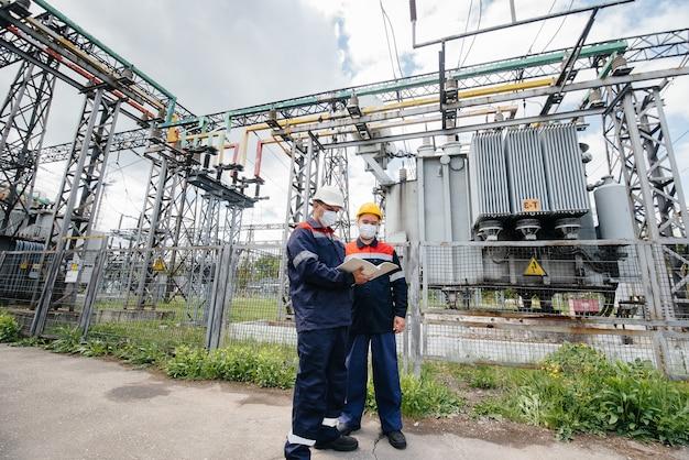 Le sottostazioni elettriche degli ingegneri conducono un'indagine sulle moderne apparecchiature ad alta tensione nella maschera al momento della pandemia. energia. industria.