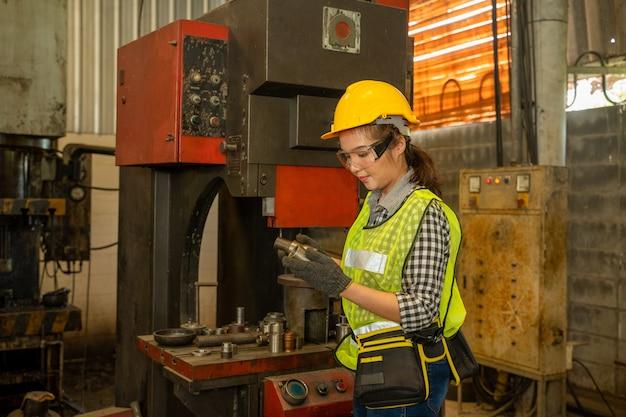 Ingegnere femmina in fabbrica d'acciaio, pesante lavoratore industriale sta lavorando sul processo di fabbrica di lavorazione dei metalli eseguendo operazioni di tornitura meccanica a macchina per l'industria delle strutture in acciaio.
