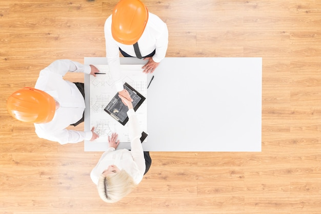 Gli ingegneri si stringono la mano vicino al progetto sul tavolo. vista dall'alto