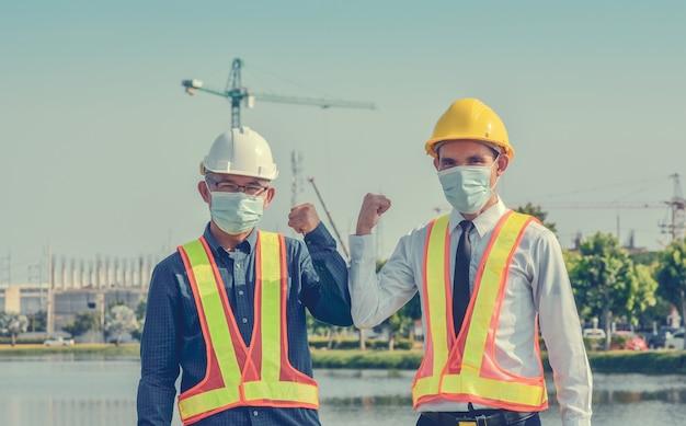Gli ingegneri si salutano a vicenda toccando i gomiti, due uomini d'affari stringono la mano senza contatto all'aperto in cantiere