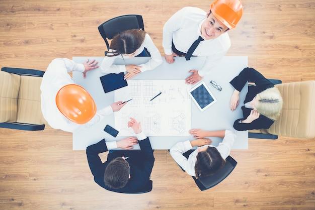 Gli ingegneri lavorano con un disegno sul tavolo. vista dall'alto