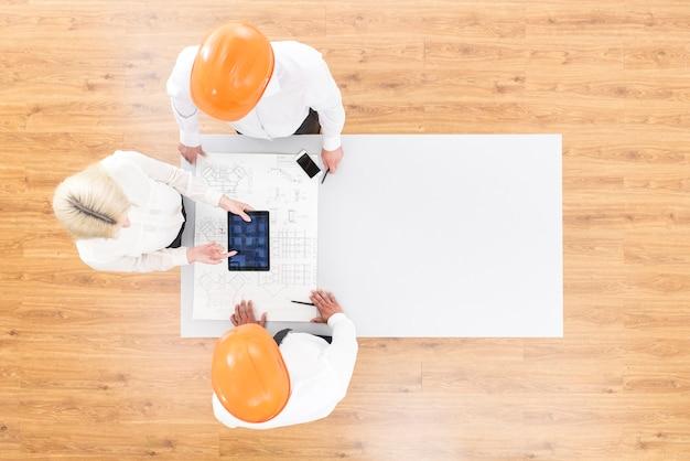 Gli ingegneri lavorano con un tablet vicino a un progetto sul tavolo. vista dall'alto