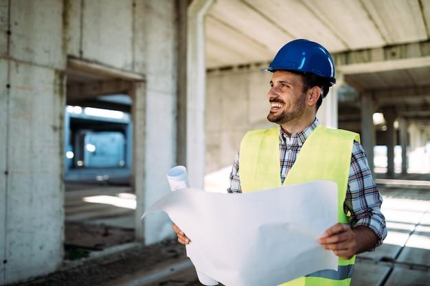 Ingegneri che lavorano in un cantiere con in mano una stampa blu