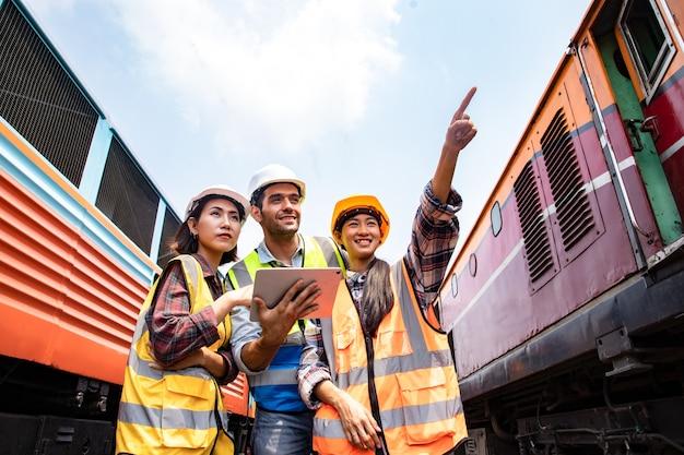 Ingegneri che lavorano sulla stazione dei treni ferroviari e tengono in mano un laptop per pianificare e incontrare