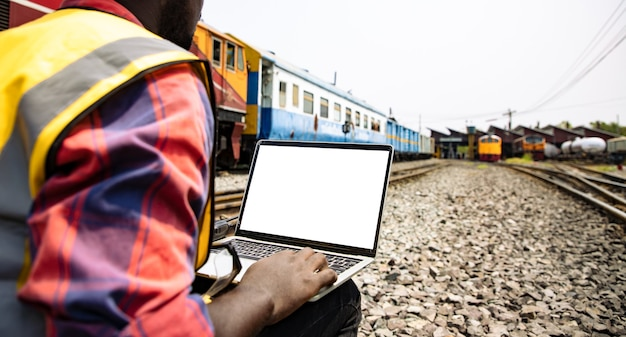 Ingegneri che lavorano sulla stazione del treno ferroviario e tengono in mano un laptop con schermo bianco per il progetto del piano
