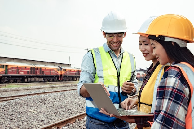 Ingegneri che lavorano alla stazione ferroviaria e che tengono un laptop