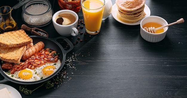 Prima colazione inglese su un tavolo scuro uova fritte con pancetta fagioli in scatola e salsiccia