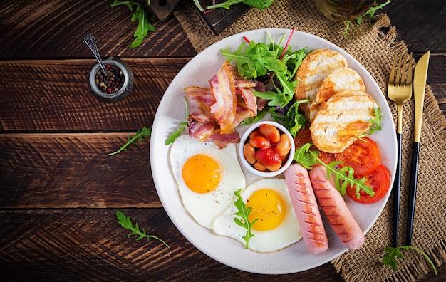 Colazione inglese: uova fritte, fagioli, pomodori, salsicce, pancetta e pane tostato