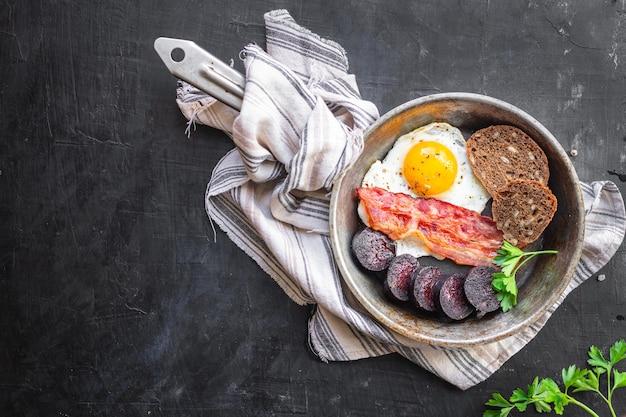 Colazione inglese uovo fritto budino nero sanguinaccio salsiccia cereali pane fagioli uova strapazzate sul tavolo