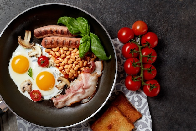 Colazione inglese. uova fritte, salsicce, bacon, fagioli, toast, pomodori su tavola di pietra. vista dall'alto con copia spazio