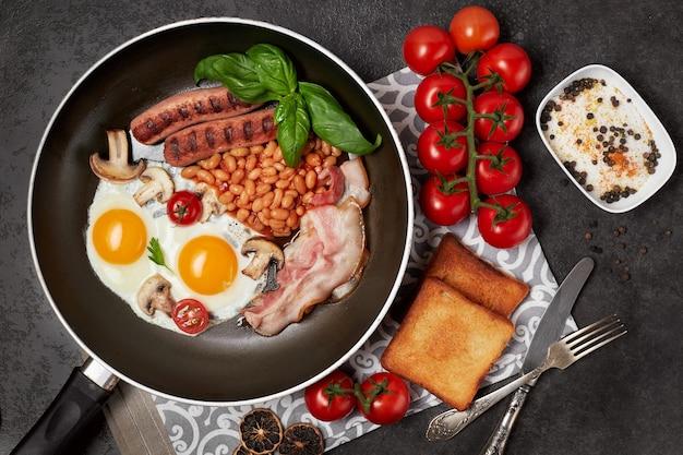 Colazione inglese. uova fritte, salsicce, pancetta, fagioli, toast, pomodori sul tavolo di pietra. vista dall'alto con copia spazio