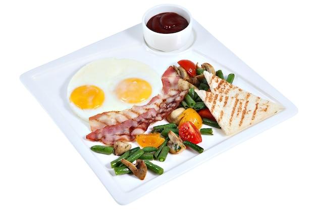 Colazione all'inglese, uova fritte con il lato soleggiato in alto con pancetta, verdure e pane tostato, sul piatto da portata quadrato isolato su sfondo bianco.