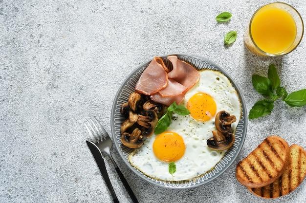 Colazione inglese. uova fritte con funghi e prosciutto con un bicchiere di succo d'arancia per colazione. buongiorno.