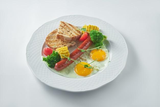 Colazione inglese: uova fritte con salsiccia, mais, pomodori, broccoli e pane di segale. variazione sana. sfondo bianco