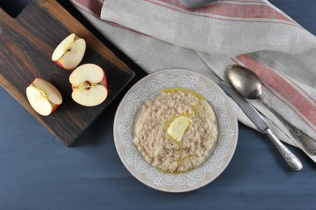 Porridge inglese della farina d'avena della prima colazione con burro e mele