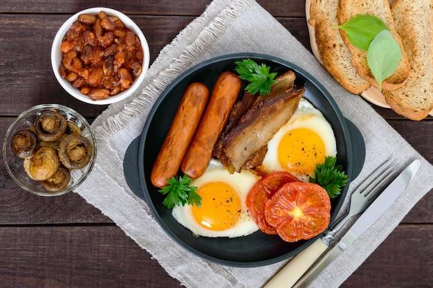 Colazione inglese: salsicce, pancetta, pomodori, uova, fagioli in salsa, funghi fritti, toast su un tavolo di legno scuro. vista dall'alto. cibo classico tradizionale dell'inghilterra.