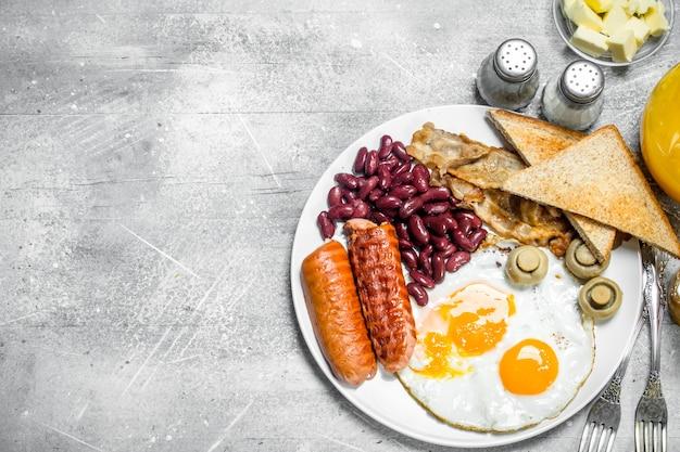 Colazione inglese. una varietà di snack con succo d'arancia su un tavolo rustico.