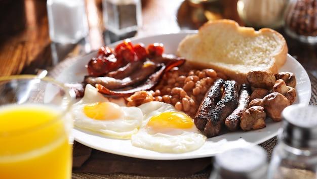 Prima colazione inglese su un piatto bianco