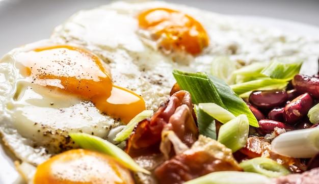 Prima colazione inglese con uova, bacon, fagioli e cipolla iyoung in piatto bianco.