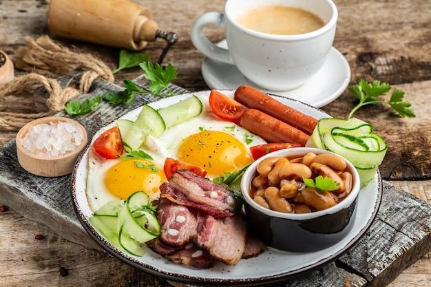 Prima colazione inglese con uovo fritto, salsiccia, pancetta, fagioli, tabella ricette alimentari. avvicinamento.
